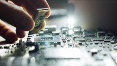 Technician plug in CPU microprocessor to motherboard socket. Workshop background